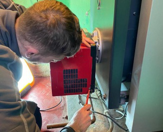 Commercial gas engineer working on commercial boiler